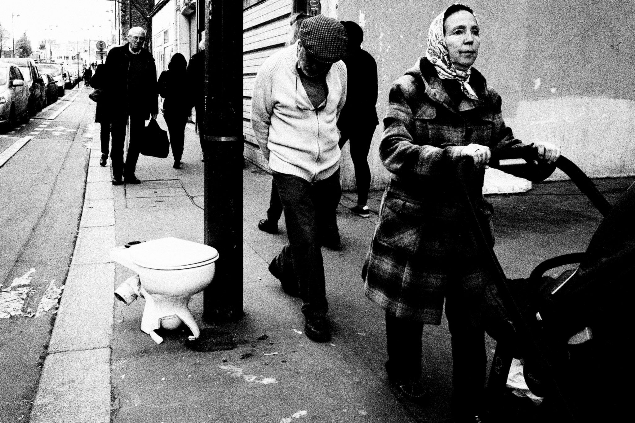 People stroll by a toilet on the street in the 19th arrondissement. Shot with a Ricoh GR2 by Jay Sennett.