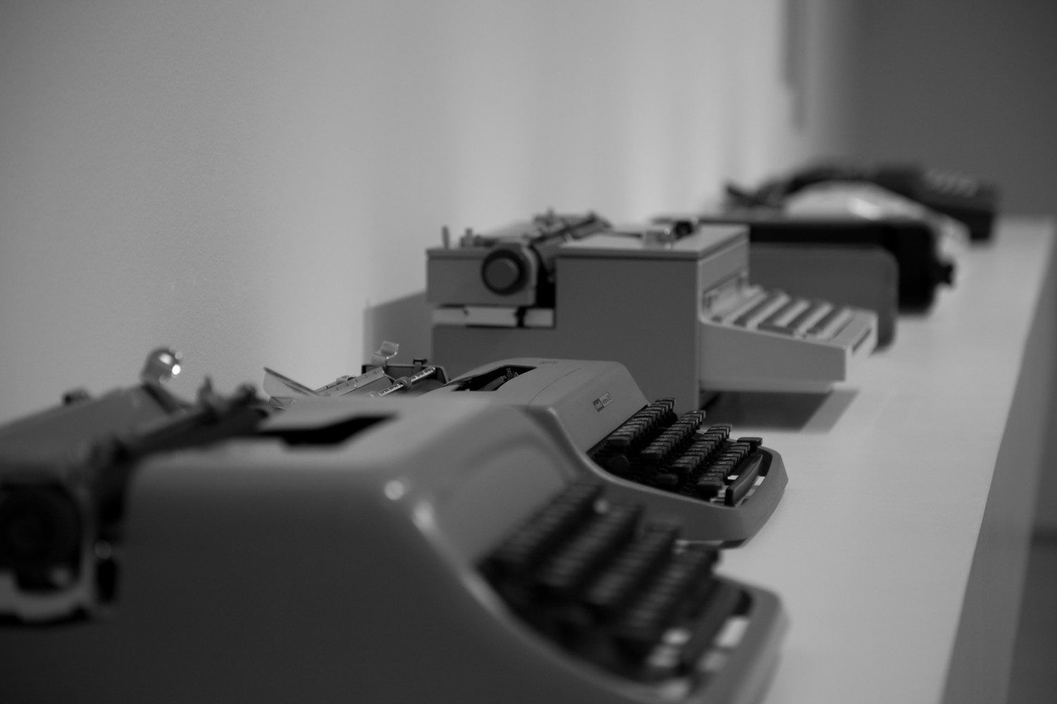 Several typewriters in a row on a long table.