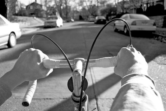 A man's hands are on the handlebars of a bicycle. as we look down the street from his point-of-view