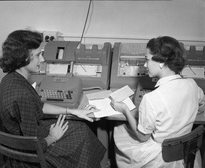 two ladies review an IBM keypunch card