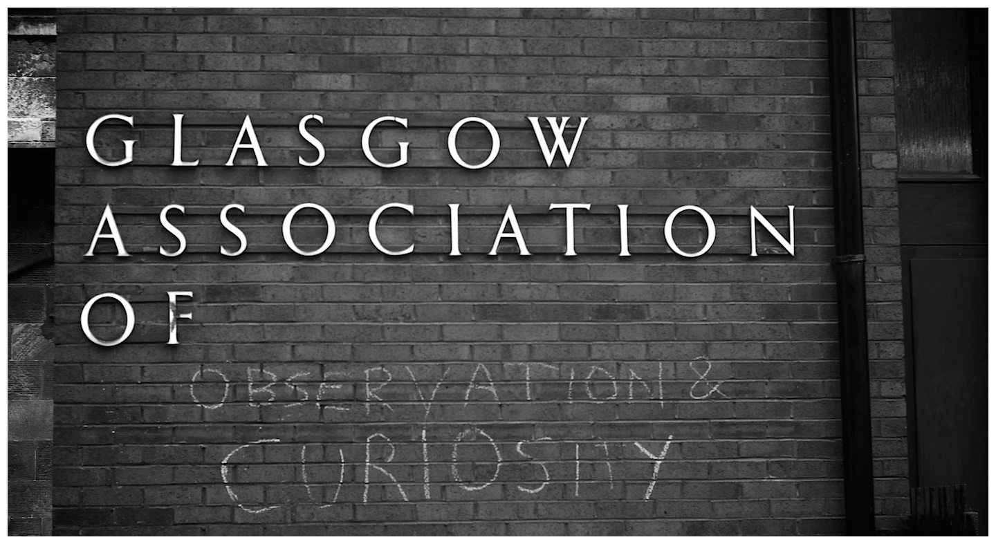 A building where Observation and Curiosity are written in chalk beneath the industrial name of the building, Glasgow Association