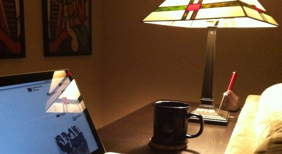 a color photo of a mac laptop, a cup of coffee bathed in light